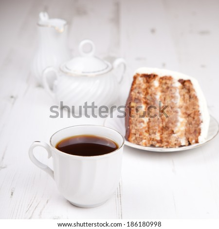 Cup of coffee with a piece of pecan cake with white buttercream icing