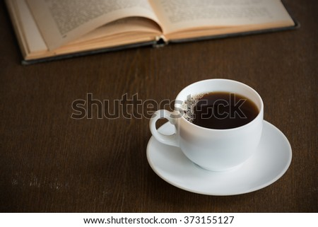 Cup of coffee with an open book on a grunge wooden table. Vignette is added.