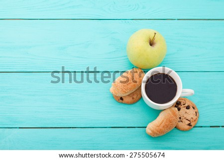 Cup of coffee with apple, croissants and cookies on blue wooden background - stock photo