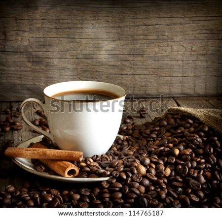 Cup of coffee with beans and cinnamon vintage still life
