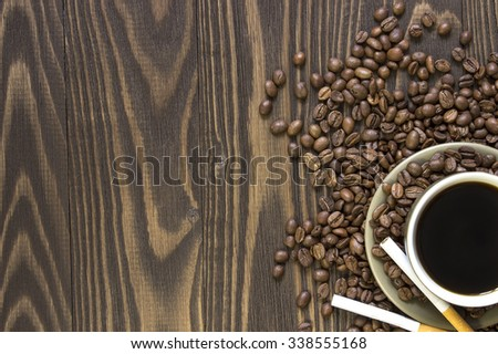 Cup of coffee  with beans, and two cigarettes  standing on a wooden table. Crop. Top view - stock photo