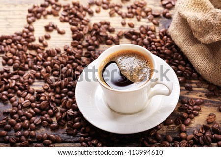 cup of coffee with beans on wooden table - stock photo
