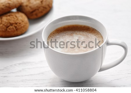 Cup of coffee with biscuits on light wooden background