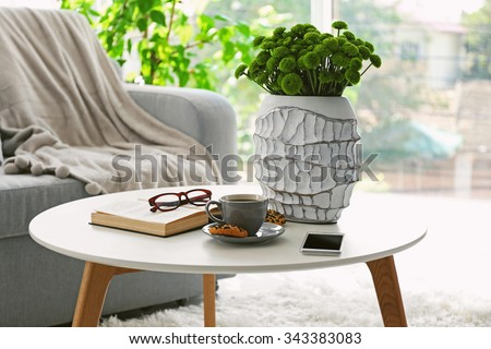 Cup of coffee with biscuits on table in room