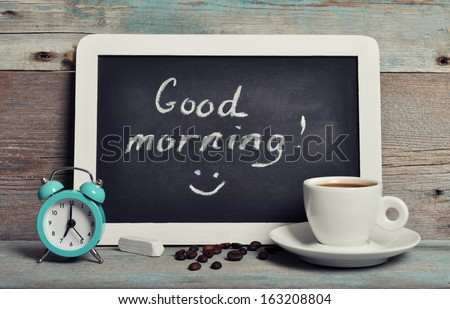 Cup of coffee with blackboard and alarm clock on vintage wooden background  - stock photo