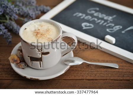 Cup of coffee with blackboard on wooden background