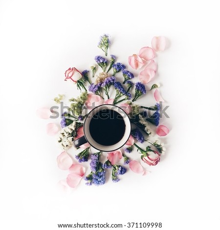 Cup of coffee with blue and pink flowers. Flat lay, top view - stock photo