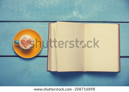 Cup of coffee with book on blue wooden table. - stock photo