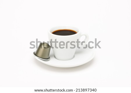 Cup of coffee with capsule on white background