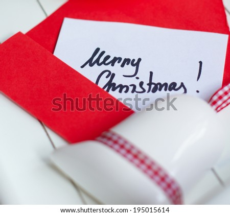 Cup of coffee with Christmas decorations and greeting card