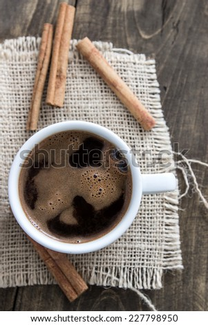 cup of coffee with cinnamon sticks on wood, rustic style - stock photo