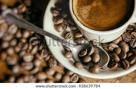 Cup of coffee with coffee beans and bokeh - stock photo