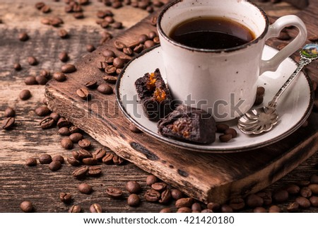 Cup of coffee with coffee beans on a wood table, close up photo - stock photo