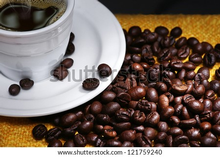 Cup of coffee with coffee beans on black background. - stock photo