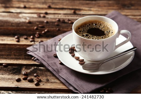 Cup of coffee with coffee beans on brown wooden background