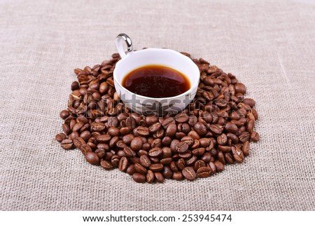 Cup of coffee with coffee beans on linen texture table - stock photo