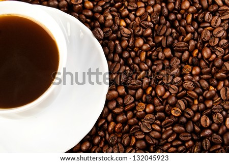 Cup of coffee with coffee beans on wood table.