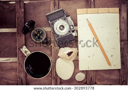 cup of coffee with compass notepad and camera on brown wood table background