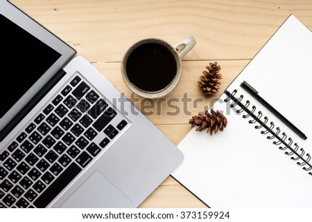Cup of coffee with computer laptop and blank notebook on wooden desk, selective focus  - stock photo