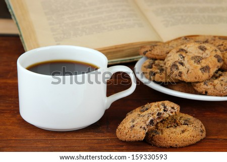 Cup of coffee with cookies and books on wooden background