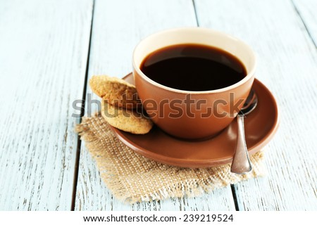 Cup of coffee with cookies and spoon on burlap cloth, on color wooden background