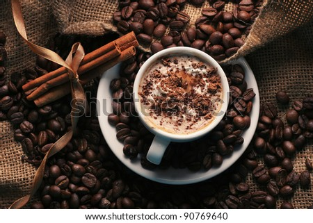 cup of coffee with cream and cinnamon on the textural fabrics - stock photo