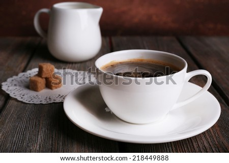 Cup of coffee with cream in milk jug and sugar cubes on wooden table on dark background