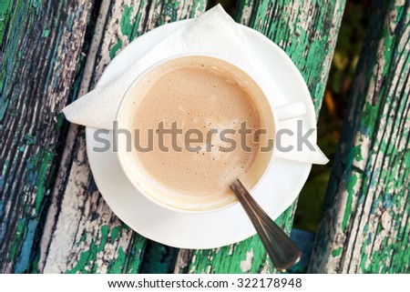 Cup of coffee with cream is on old wooden bench in autumn park.  Top view, selective focus with shallow DOF - stock photo