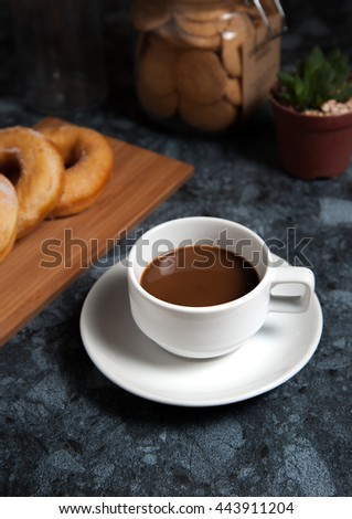 Cup of coffee with delicious donuts with icing and in plate on black marble table.