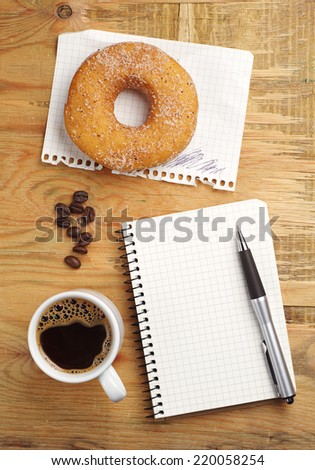 Cup of coffee with donut and opened notepad on desk. Top view - stock photo