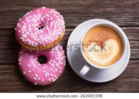 Cup of coffee with donuts on wooden background - stock photo