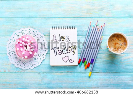 Cup of coffee with doughnut, crayons and note LIVE TODAY on wooden background - stock photo