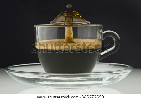 Cup of coffee with drop explosion on black background