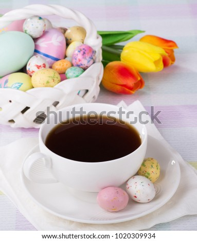 Cup of coffee with Easter candy on saucer with basket of treats and flowers in background