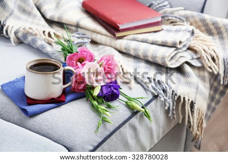 Cup of coffee with flowers near books on sofa in room - stock photo