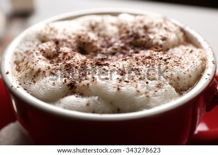 Cup of coffee with foam and chocolate powder closeup