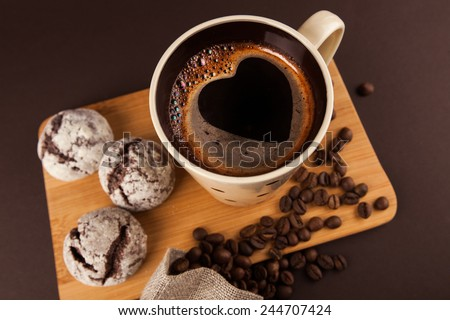 Cup of coffee with foam, heart shaped, with cookies and coffee beans, lying on the wooden stand, on brown background - stock photo