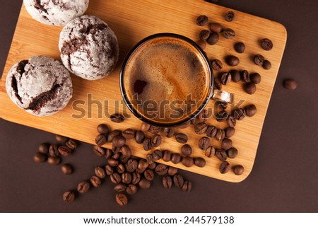 Cup of coffee with foam, with cookies and coffee beans, lying on the wooden stand, on brown background - stock photo