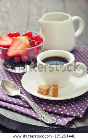Cup of coffee with fresh berries on vintage wooden background closeup