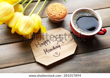Cup of coffee with fresh cupcake, tulips and Happy Monday massage on wooden background - stock photo