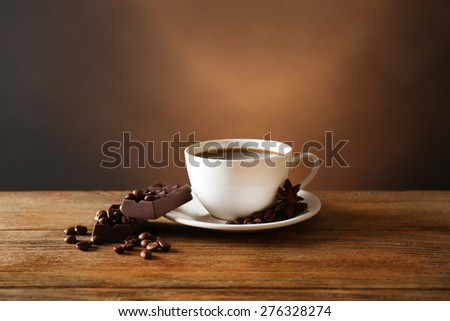 Cup of coffee with grains and chocolate on wooden table on dark background - stock photo
