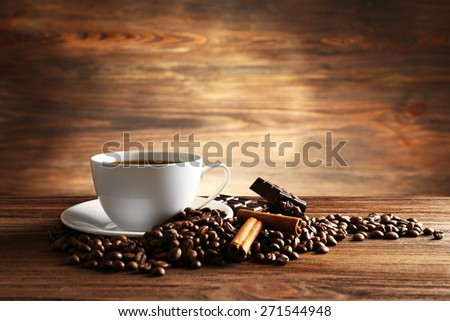 Cup of coffee with grains, chocolate and cinnamon sticks on wooden background - stock photo