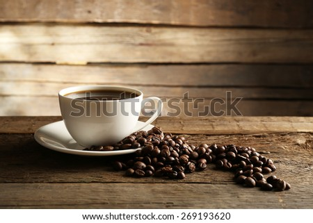 Cup of coffee with grains on wooden background - stock photo