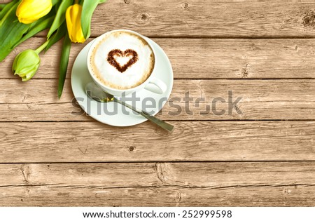 Cup of coffee with heart and yellow tulips on the wooden background - stock photo