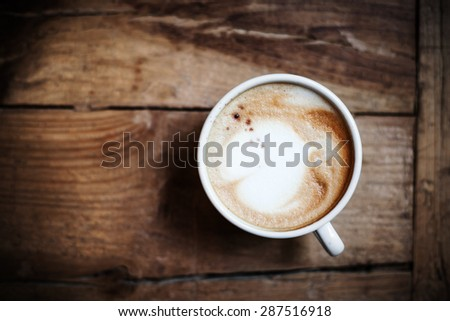 Cup of coffee with heart pattern in a white cup on wooden background. Latte Art, top view. - stock photo