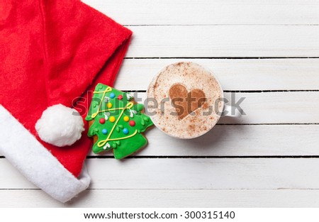 Cup of coffee with heart shape and christmas gingerbread on white wooden background. - stock photo