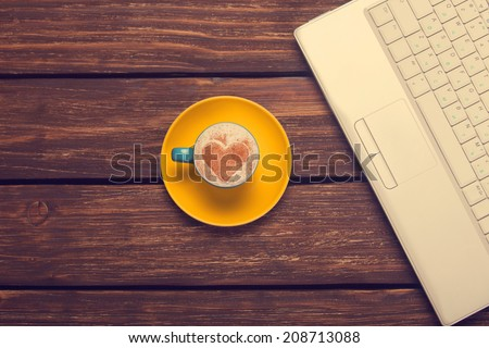 Cup of coffee with heart shape and notebook on wooden table. - stock photo