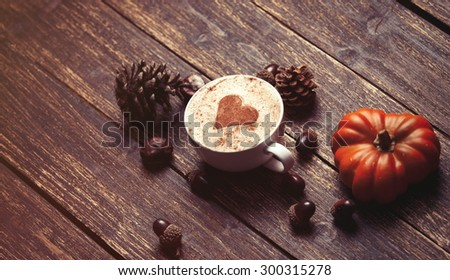Cup of coffee with heart shape and pine cone with acorn and pumpkin on wooden background - stock photo
