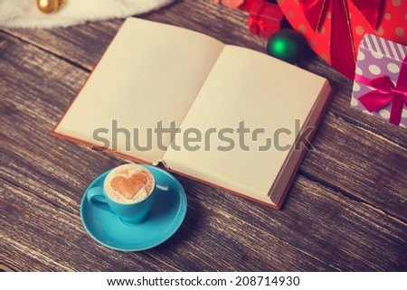 Cup of coffee with heart shape, book and christmas gifts. - stock photo