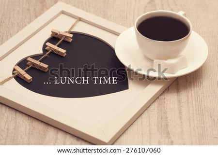 cup of coffee with heartshaped chalkboard indicating LUNCH time on the wooden background - stock photo